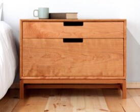 Wooden chest of drawers next to a bed