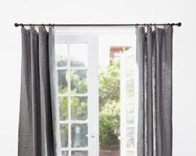 Drapes hanging in front of an open window