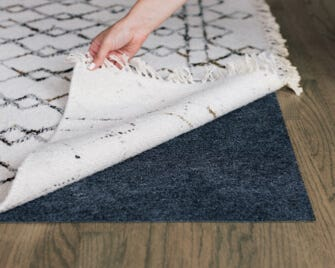 Interior Define Rug being placed over a rug pad